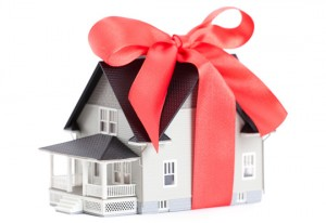 Real estate concept - house architectural model with red bow on it, isolated